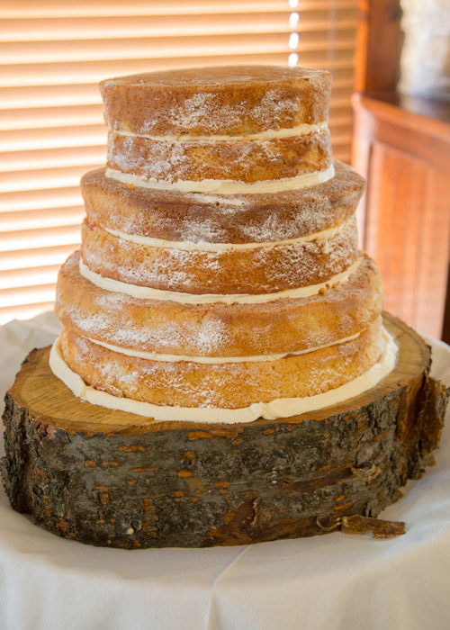 naked cake before it's decorated in front of blind on wooden block