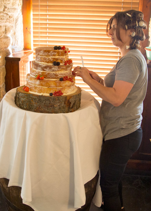 lady with rollers in her hair decorating the cake