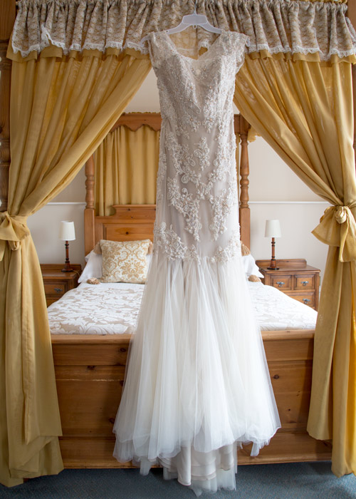 wedding dress on four poster bed with matching drape