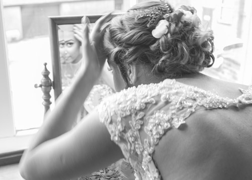 bride chacking her makeup in a mirror black and white