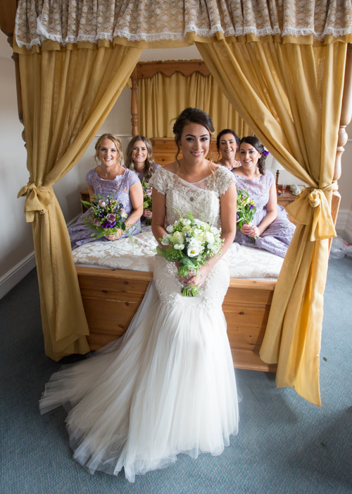 bride and bridesmaids sitting on four poster bed at cubley hall hotel sheffield