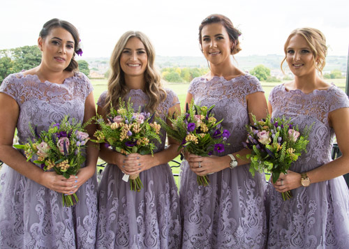 bridesmaids in purple dresses with cubley penistone in the background
