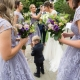 bridesmaids picking confetti out of brides hair in purple bridesmaid dresses