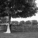 bride and groom under tree with landscape background