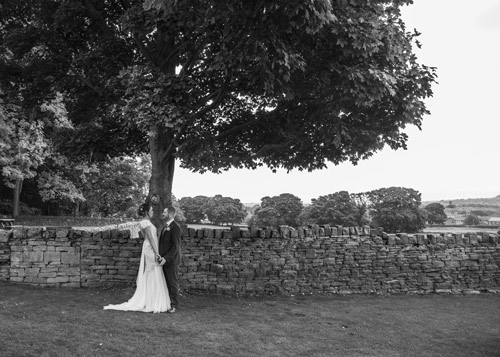 black and white bride and groom holding hands under tree cubley hall penistone sheffield