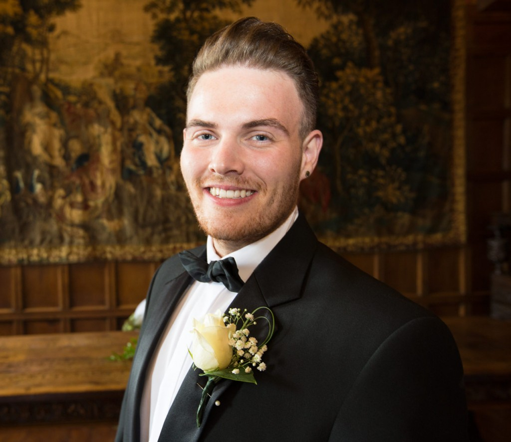 close up of groom with 18th century tapestry in the background