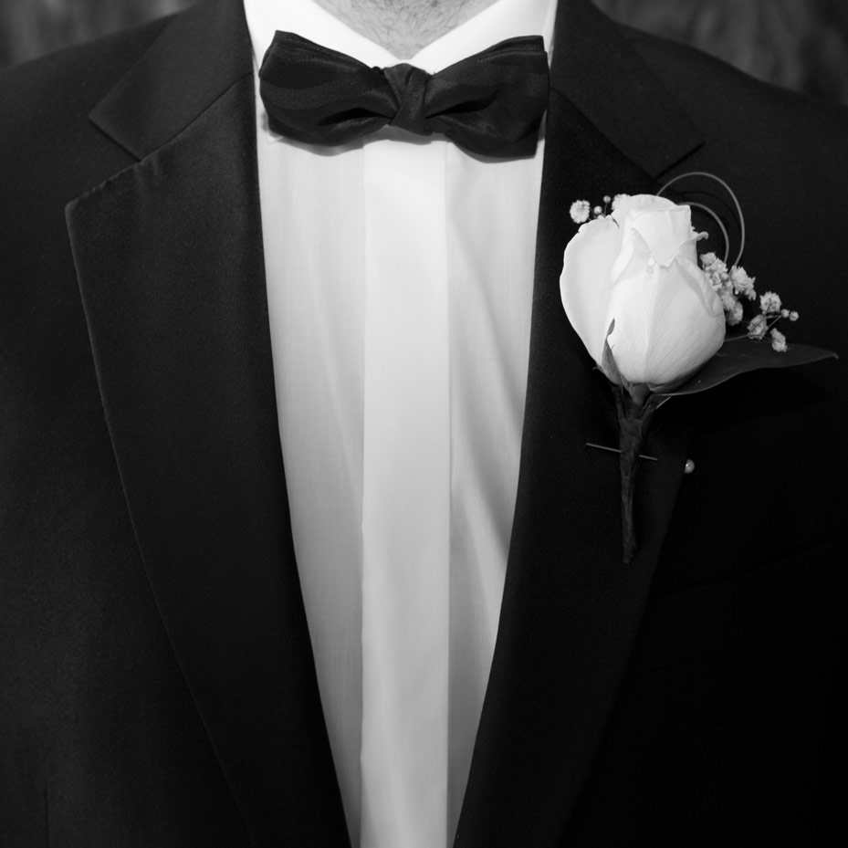groom with bowtie and white button hole