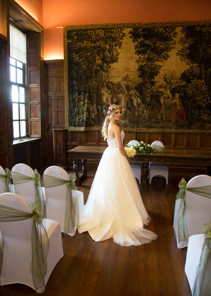 bride looking over her shoulder in wedding dress holding white flowers