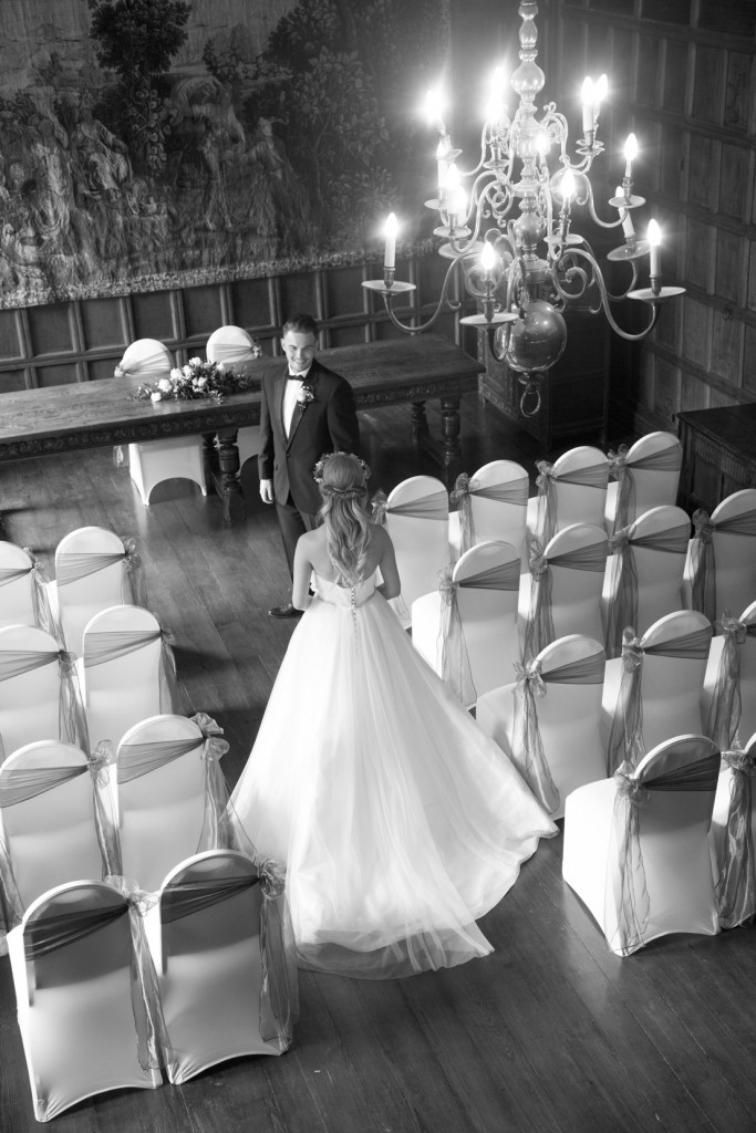 bride walking towards groom with chandelier in foreground in cannon hall barnsley ballroom