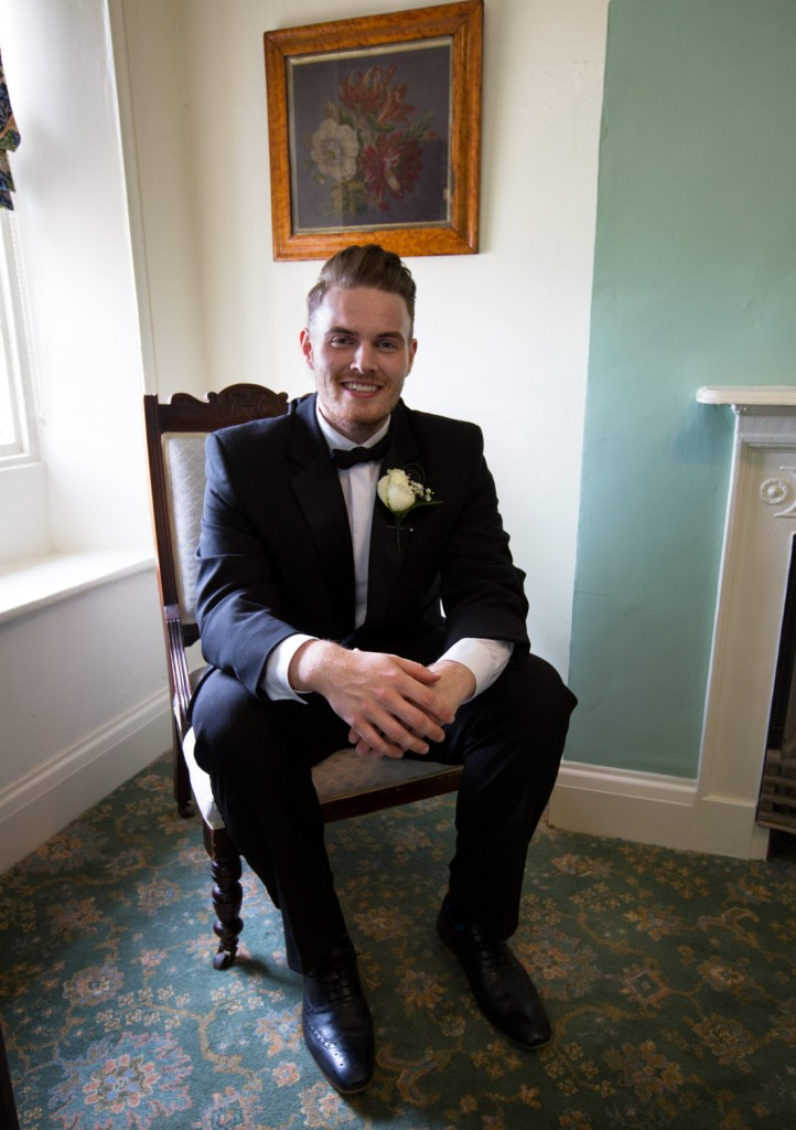 groom sitting on a chair in the butlers pantry in ashworth and bird suit