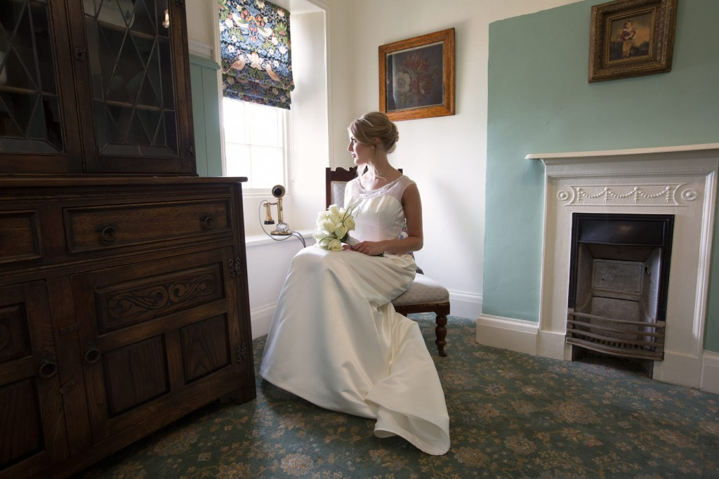 bride looking out of the window of the butlers pantry barnsley museums wedding