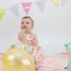 baby girl with bunting and balloons