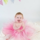 toddler in pink tutu with bunting in background