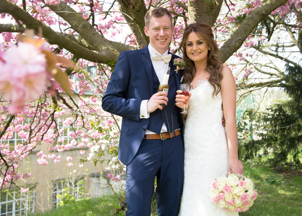 couple with drinks under blossom tree the stables high melton doncaster