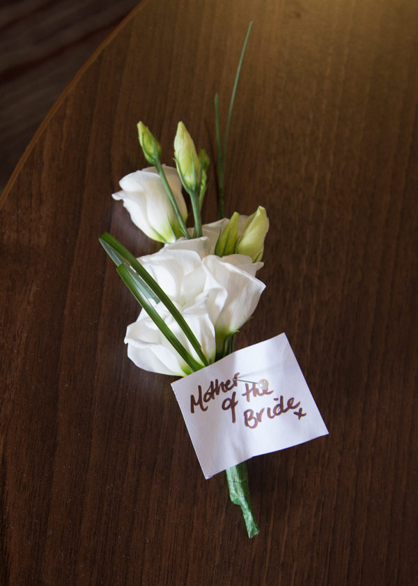 mother of the bride buttonhole on wooden table