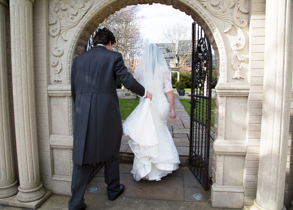 groom holding brides dress walking into holiday inn barnsley secret garden