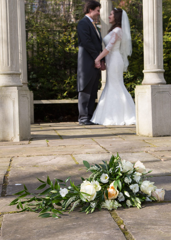 orange and white bouquet with bride and groom in background holiday inn barnsley secret garden