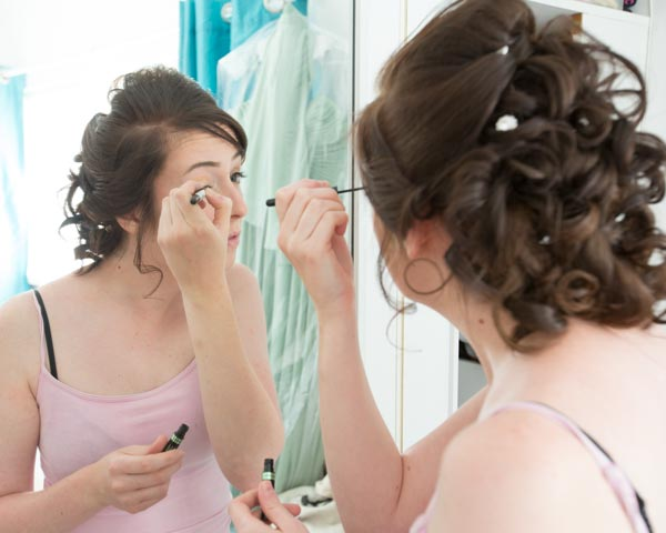 woman in pink top applying eyeliner