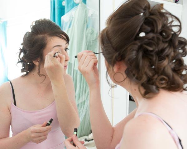 woman in pink top applying eyeliner