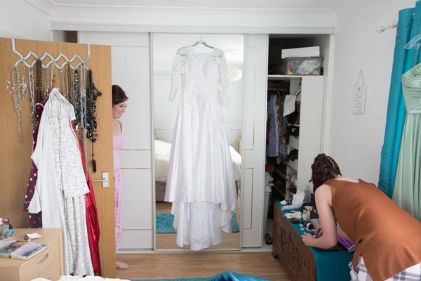 wedding dress hanging on mirror while ladies get ready
