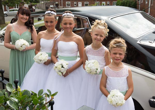 bridesmaids in mint green dresses next to the wedding car