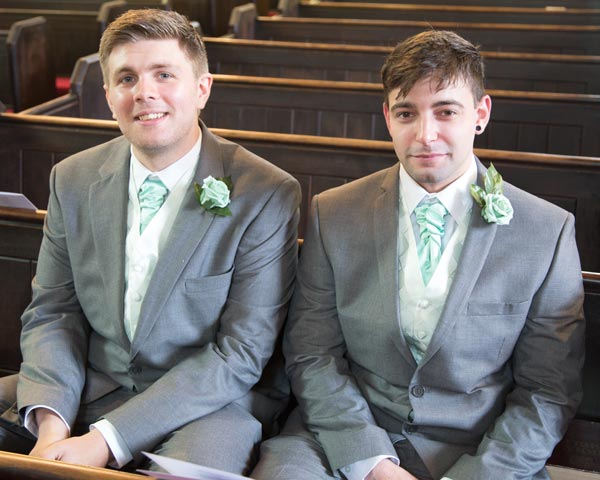groom and best man in green and grey suits waiting in church