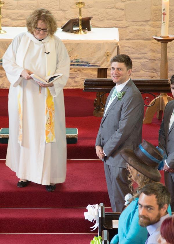 groom looking over his shoulder smiling christ church ardsley barnsley