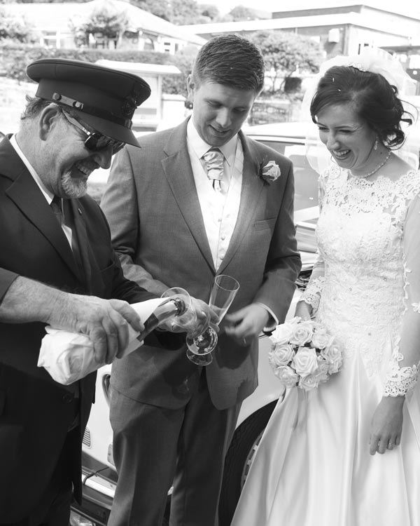 chauffer pouring champagne for bride and grom black and white