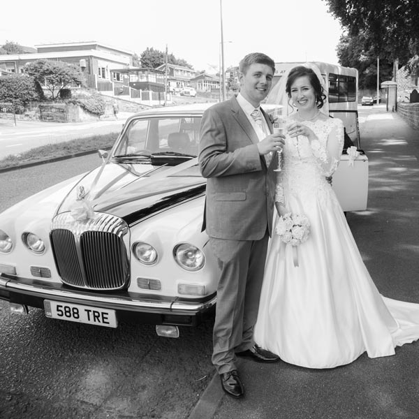 married couple with champagne in front of wedding car outside christ church ardsley barnsley
