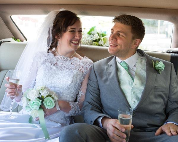 newlyweds in back of wedding car outside christ church ardsley barnsley