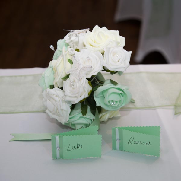 mint green and white artificial bouquet and name cards rigby suite barnsley premier leisure