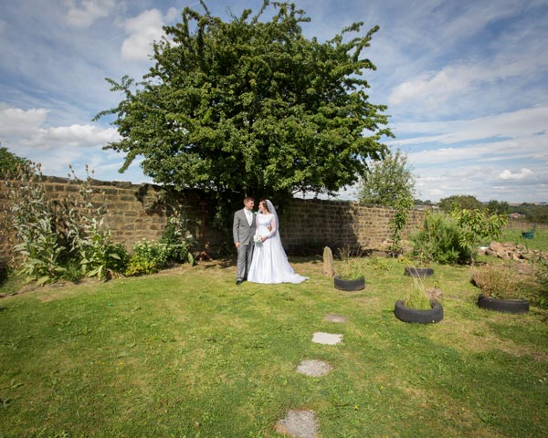 bride and groom in front of tree at carers garden metrodome barnsley