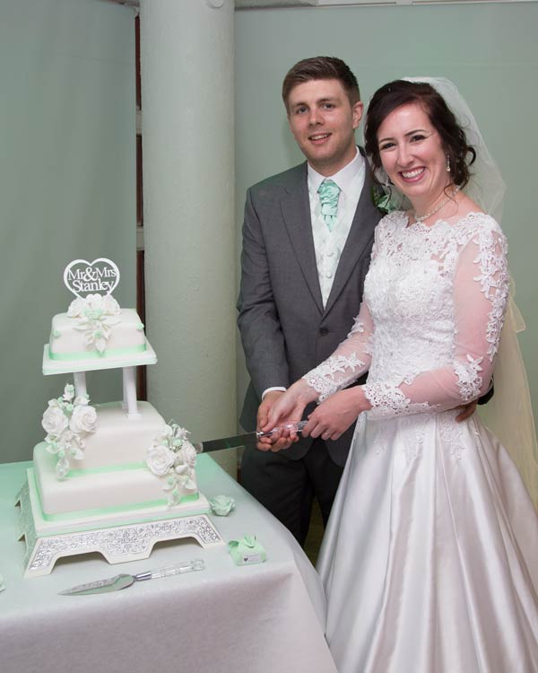 newlywed couple cutting three tier cake rigby suite wedding barnsley premier leisure