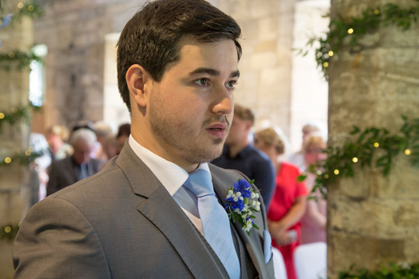 Groom with black hair and blue tie waiting for bride york hospitium