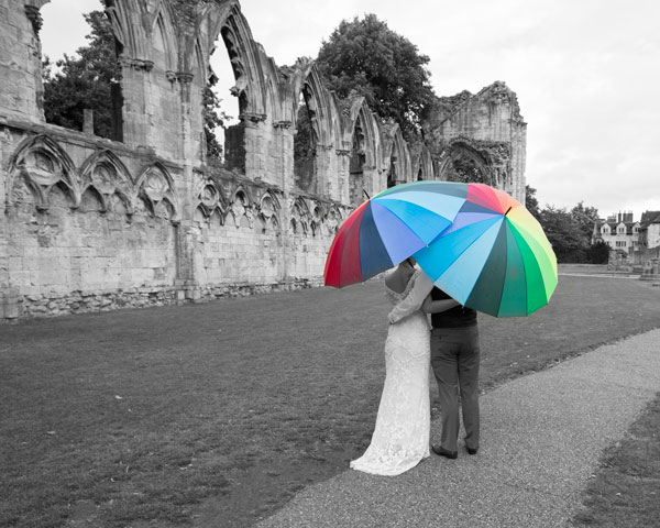 bride and groom with colourful umbrellas york museum wedding