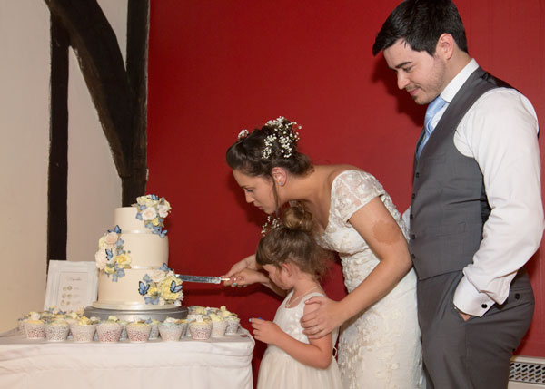 bridesmaid helping to cut the wedding cake