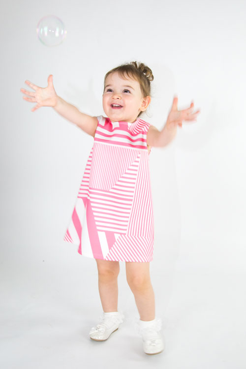 toddler in pink dress chasing bubbles studio photographer barnsley
