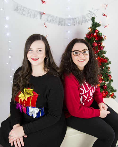 two girls in christmas jumpers against white background christmas shoot ideas