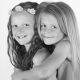 black and white two girls hugging against a white backdrop