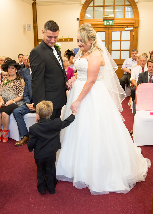 couple holding sons hand during wedding ceremony sheffield town hall south yorkshire