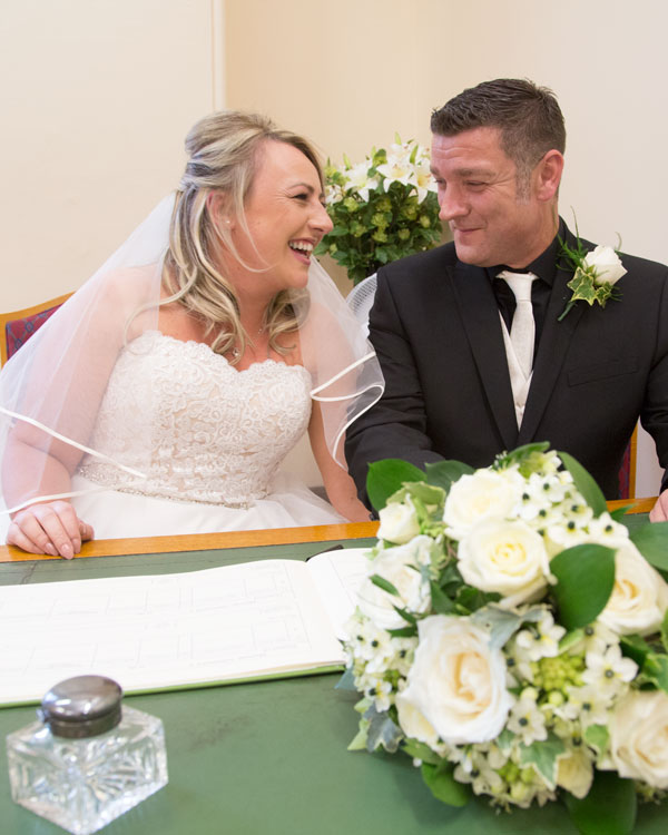 couple looking at each other while signing the register sheffield wedding photographer