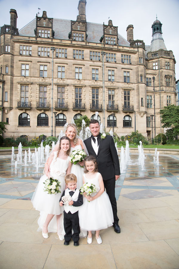 Bride and groom with bridesmaids and page boy in front of the peace garden fountains sheffield wedding photographer