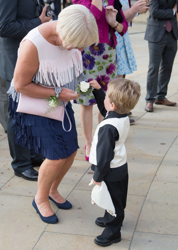 Boy giving flower to wedding guest in peace gardens sheffield
