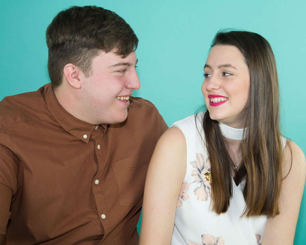 engaged couple in blue backdrop looking at each other pre wedding shoot barnsley