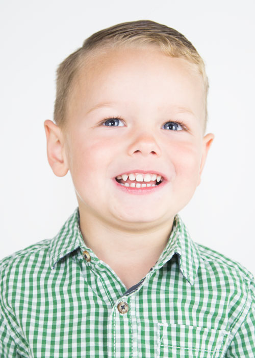 boy in green shirt smiling against white background family photographers in barnsley