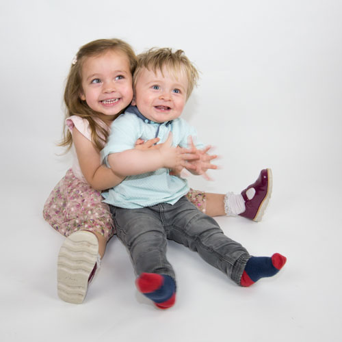 girl in pink dres holding boy in blue top and jeans family photography barnsley