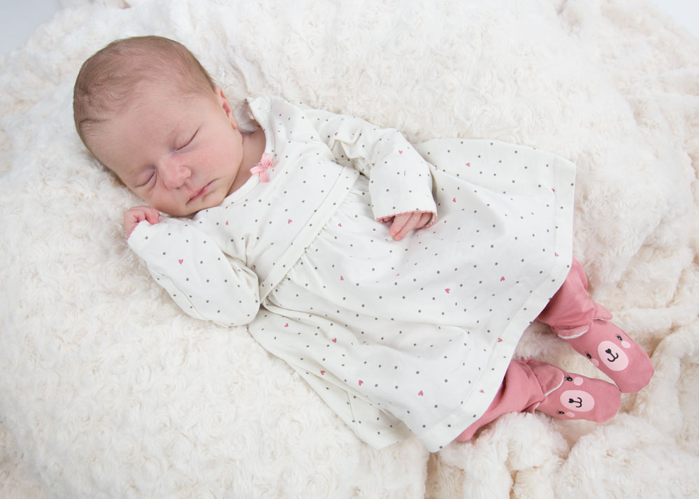 newborn photographer barnsley baby in white dress and pink tights