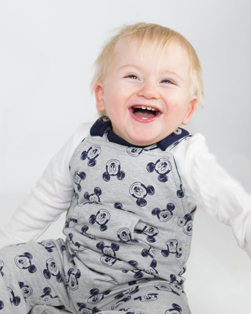 Toddler laughing in blue dungarees on white background