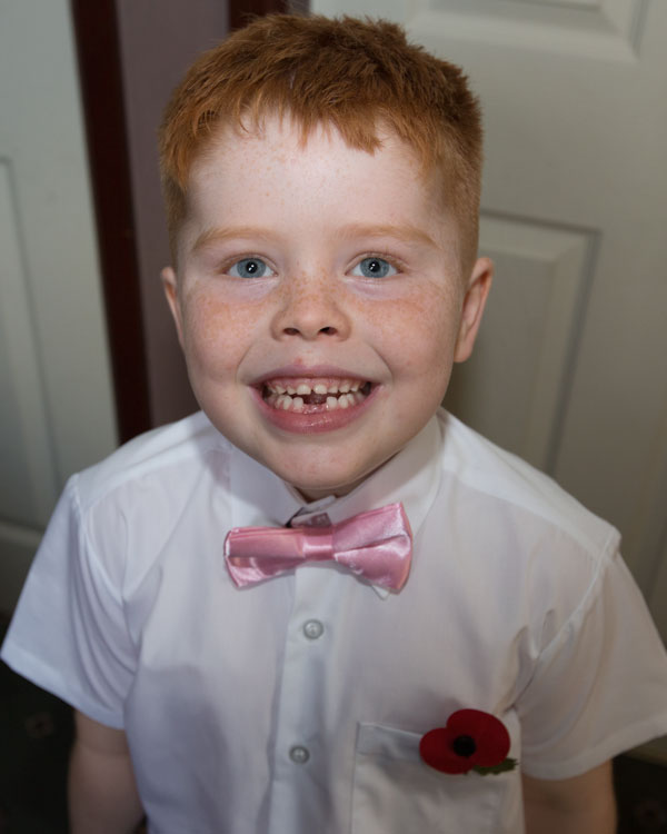 pageboy looking up at camera in white shirt and pink bow tie