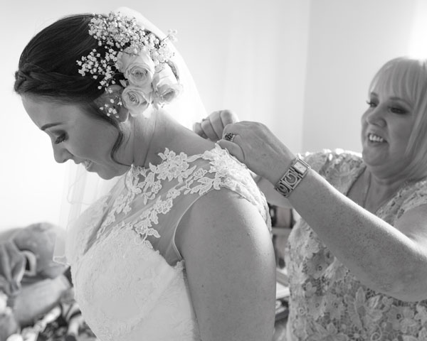 Mother of the bride fastening the wedding dress black and white